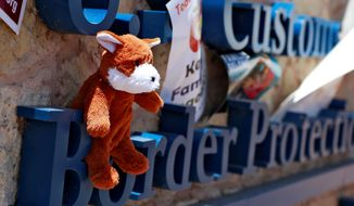 A teddy bear is left on the sign of U.S. Customs and Border Protection on Tuesday, in Fabens, Texas, along the border where immigrant children are being held. A group tried to deliver items to the children housed in tents at the facility but were turned away. (ASSOCIATED PRESS)