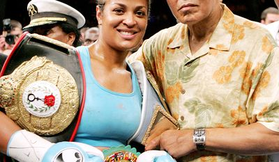 Boxer Laila Ali, left, poses with her father, boxing great Muhammad Ali, after her win against Erin Toughill, at the MCI Center in Washington.  (AP Photo/Pablo Martinez Monsivais)
