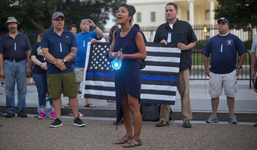 Michelle Malkin, center, a blogger and political commentator, leads a gathering of supporters of law enforcement officers carried blue lights during a pro-police rally held in front of the White House in Washington, Friday, July 22, 2016. (AP Photo/Pablo Martinez Monsivais)