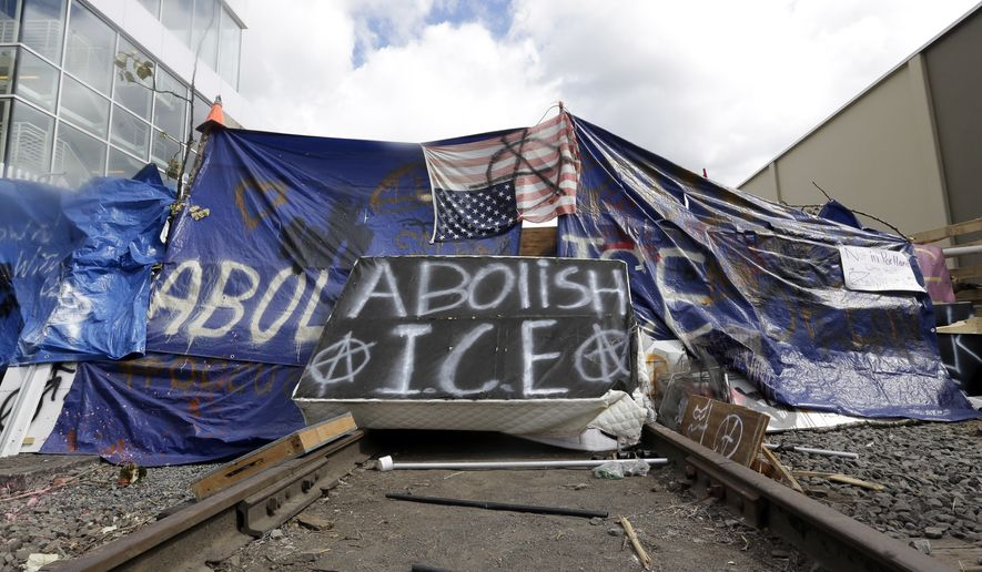 A barricade crosses railroad track at a protest camp on property outside the U.S. Immigration and Customs Enforcement office in Portland, Ore., Monday, June 25, 2018. Law enforcement officers began distributing notices to vacate to demonstrators late Monday morning. The round-the-clock demonstration outside the Portland headquarters began June 17, 2018, and increased in size early last week, prompting officials to close the facility. (AP Photo/Don Ryan)
