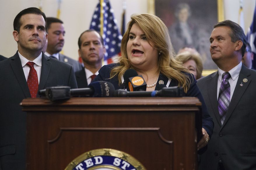 Puerto Rico's Resident Commissioner, Jenniffer González-Colón, speaks during a ceremony on Capitol Hill in Washington, Wednesday, June 27, 2018, to present the Puerto Rico Admission Act of 2018, a bill to chart Puerto Rico's transition from a territory to a State of the Union. She is joined by Puerto Rico Gov. Ricardo Rosselló, left, Rep. Don Bacon, R-Neb., right, and others (AP Photo/Carolyn Kaster)