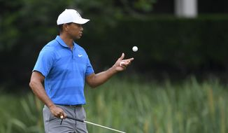Tiger Woods catches his ball on the third hole during the Quicken Loans National golf tournament Pro-Am, Wednesday, June 27, 2018, in Potomac, Md. (AP Photo/Nick Wass)