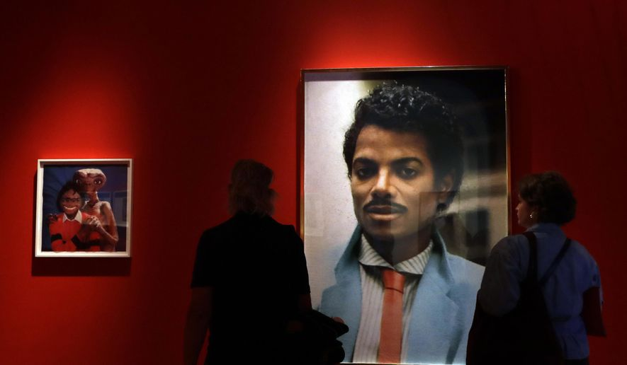 Visitors look at an artwork by Hank Willis Thomas on display at the Michael Jackson: On The Wall exhibition at the National Portrait Gallery in London, Wednesday, June 27, 2018. TA new art exhibition in London depicts Michael Jackson as a savior, a saint, an entertainer, an icon, a monarch, a mask and a mystery. The National Portrait Gallery show explores how many contemporary artists have been drawn to the late King of Pop, as an artistic inspiration, a tragic figure and a fascinating enigma. The exhibition runs at the gallery from June 28 until Oct. 21. (AP Photo/Kirsty Wigglesworth)
