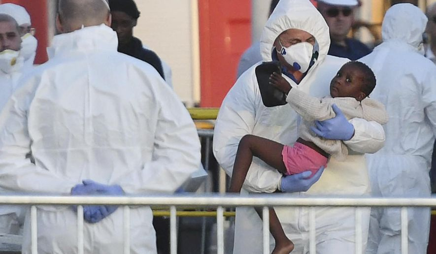 A child is disembarked from the ship operated by German aid group Mission Lifeline, carrying 234 migrants, after it docked at the Valletta port in Malta, following a journey of nearly a week while awaiting permission to make landfall, Wednesday, June 27, 2018. Eight European nations agreed to accept the passengers who qualify as refugees. (AP Photo/Jonathan Borg)