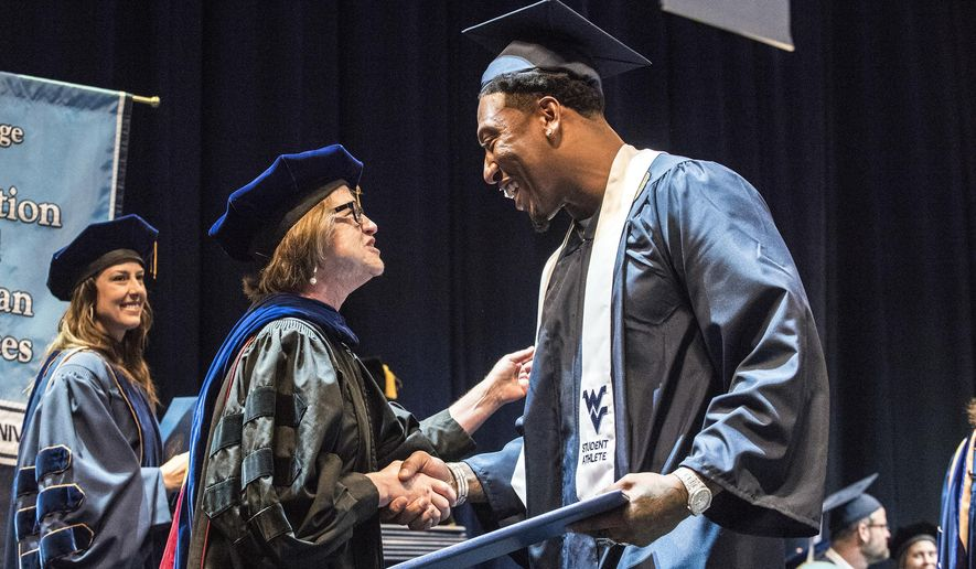 In this May 12, 2018, photo released by West Virginia University, former West Virginia University and current Oakland Raiders football player Bruce Irvin, right, receives his Regents degree from Dean Gypsy Denzine during the College of Education and Human Services Commencement in the Coliseum in Morgantown, W.Va. When Irvin got a multimillion signing bonus after being a first-round draft pick in 2012, the idea of getting his college degree was the last thing on his mind. But after having a son, the former high school dropout made getting that degree a priority and was one of many NFL players this offseason who got to don a cap and gown instead of a helmet. (West Virginia University/Brian Persinger via AP)