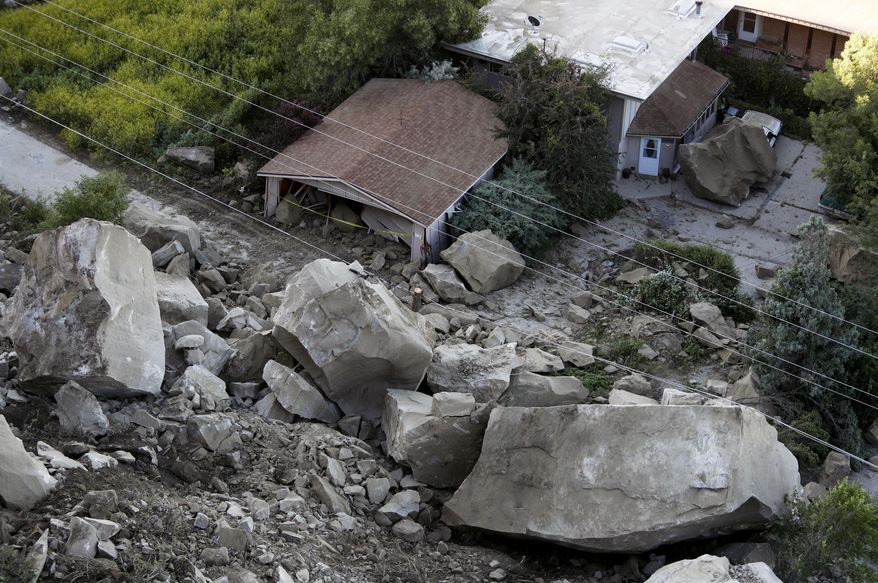 Boulders are scattered along a hillside and onto a property along the 220 block of Mountain View Blvd. following a rock slide, Wednesday, June 27, 2018, in Billings, Mont. (Casey Page/The Billings Gazette via AP)