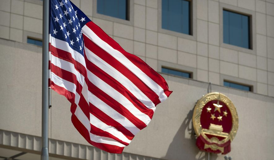 The American flag flies near the national emblem of China outside of the Bayi Building before a welcome ceremony for U.S. Defense Secretary Jim Mattis in Beijing, Wednesday, June 27, 2018. (AP Photo/Mark Schiefelbein, Pool)