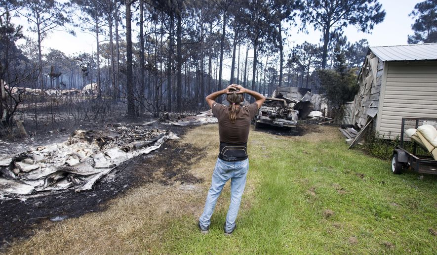 FILE- This June 25, 2018 shows Faron Bryant looking over his property after wildfires swept through his neighborhood on Ridge Road in Eastpoint, Fla. Bryant's home only lost its siding, but his workshop, a truck and boat were destroyed. Adam Putnam, Florida's agriculture commissioner, said Wednesday, June 27, 2018, that a controlled burn by state contractors sparked a wildfire that destroyed 36 homes and burned more than 800 acres. (AP Photo/Mark Wallheiser, File)