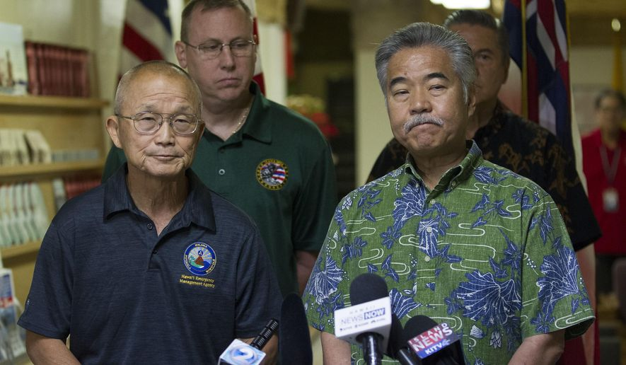FILE - In this Jan. 13, 2018, file photo, Vern Miyagi, administrator of the Hawaii Emergency Management Agency (HEMA), left, and Hawaii Gov. David Ige listen as they address the media during a news conference at HEMA at Diamond Head in Honolulu, following the false alarm issued of a missile launch on Hawaii. An employee of the Hawaii agency that mistakenly sent cellphone and broadcast alerts warning of a missile attack in January says he saw staff members watching movies or TV on the job. (George F. Lee/Honolulu Star-Advertiser via AP, File)