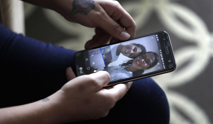 During an interview with The Associated Press Wednesday, June 27, 2018, in Evanston, Illinois,  Lidia Karine Souza, who is seeking asylum from Brazil, flips through her phone at photographs of her and her son Diogo as she talks about the ordeal she has lived in searching for and finally seeing her son for the first time on Tuesday. It took Souza weeks to find Diogo after he was taken from her at the Texas border in late May and sent by the government to a Chicago shelter.   (AP Photo/Charles Rex Arbogast)