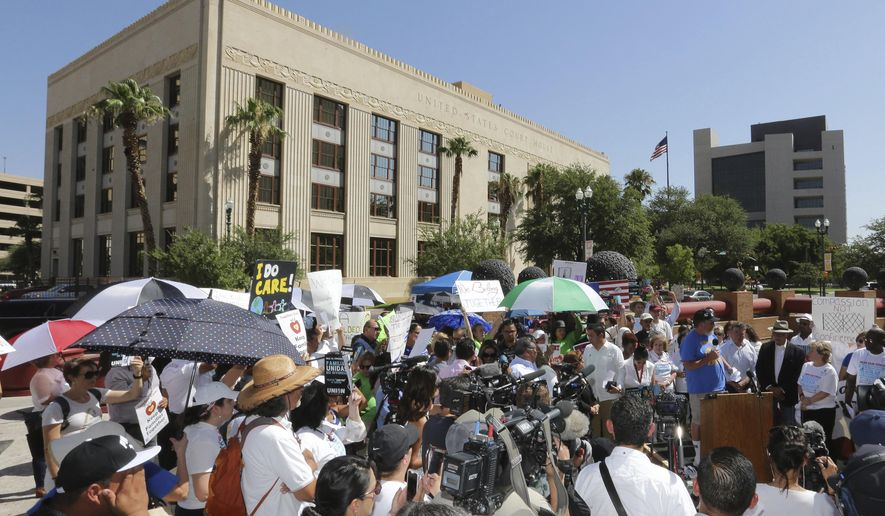 People protest immigration separation policies outside Federal Court, Tuesday, June 26, 2018, in El Paso, Texas. Cases of children and families seeking refugee were being heard inside the courthouse. (AP Photo/Matt York)