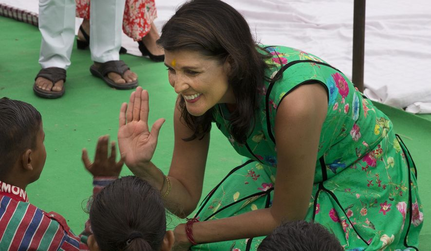 U.S. Ambassador to United Nations Nikki Haley gives a high five to a child at Mukhti Ashram, a shelter for rescued child labor, in New Delhi, India, Wednesday, June 27, 2018. Haley is on a two day visit to India during which she will meet Indian prime minister, senior Indian officials, business leaders and students. (AP Photo/Manish Swarup)