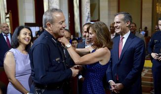 The newly named Los Angeles Police Chief Michel Moore, gets pinned by his wife, Cindy, right, during his swearing-in ceremony in the Los Angeles City Council Chambers Wednesday, June 27, 2018, as council members from left,, Nury Martinez, Herb Wesson, Mitch Englander, and Mayor Eric Garcetti, far right, look on. Moore replaces Charlie Beck, who retired after more than 40 years with the LAPD.   (David Crane/Los Angeles Daily News via AP)