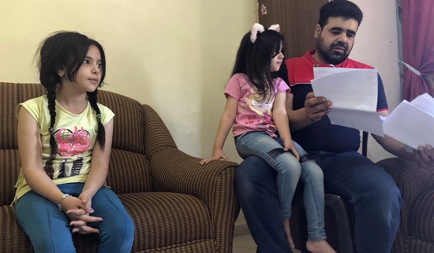 Syrian refugee Mahmoud Mansour, sitting with his daughters Sahar, 5, and Ruba, 11, holds documents for his U.S. resettlement application at his rented apartment in Amman, Jordan, Wednesday, June 27, 2018. Mansour who had been tapped for possible resettlement to the United States says his hopes have been crushed for good by the Supreme Court's decision to uphold a Trump administration travel ban for Syria and four other Muslim-majority countries. (AP Photo/Omar Akour)