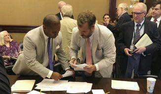 House Minority Leader Todd Rutherford, left, and state Rep. Kirkman Finlay, right, sign a compromise proposal that would temporarily lower electric rates for South Carolina Electric & gas customers 15 percent on Wednesday, June 27, 2018, in Columbia, SC. The House and Senate will consider the bill which nearly eliminates rate increases used to pay for two nuclear reactors that were never built. (Jeffrey S. Collins / Associated Press)