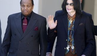 FILE - In this March 15, 2005 file photo, Pop star Michael Jackson leaves the Santa Barbara County Courthouse with his father, Joe, in Santa Maria, Calif., following a day of testimony in Jackson's trial on charges of child molestation.  Joe Jackson, the patriarch of America's most famous musical clan has died, says a family source on Wednesday, June 27. He was 89. (AP Photo/Michael A. Mariant, File)