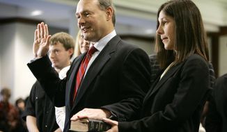 In this Jan. 2, 2007 file photo Iowa State Treasurer Michael Fitzgerald takes the oath of office as his fiance Susan Lowery, right, holds his Bible during a swearing-in ceremony for statewide elected officials in Des Moines, Iowa. Iowa politicians are scrambling to comply with a new and unusual state law that bans them from using taxpayer dollars if there's a whiff of self-promotion. The Iowa Ethics and Campaign Disclosure Board plans to release at least one advisory opinion next month on the law, which goes into effect Sunday, July 1, 2018. The provision prohibits statewide officials and lawmakers from tapping taxpayer dollars to promote their written name, likeness or voice through various platforms like television and radio. (AP Photo/Charlie Neibergall, file)