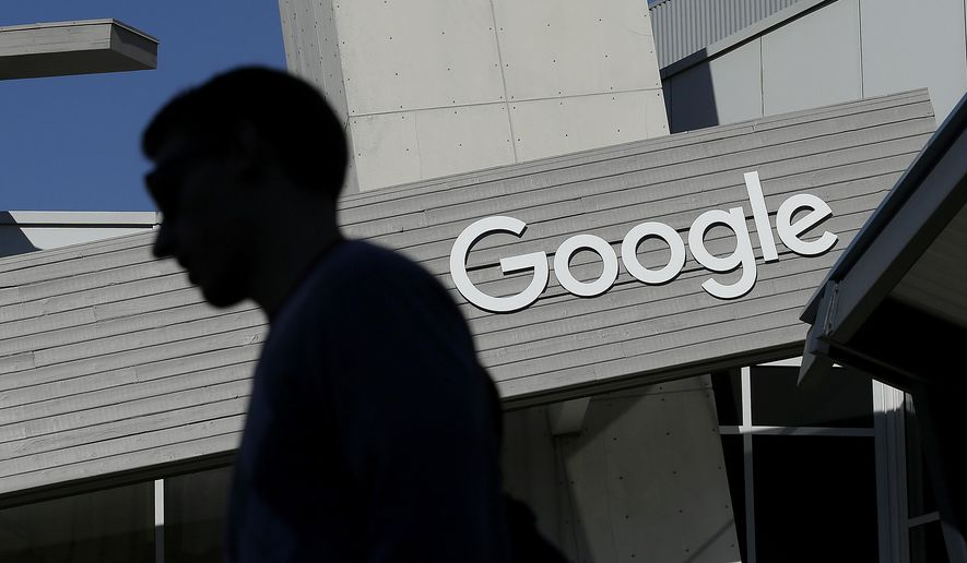 In this Nov. 12, 2015, file photo, a man walks past a building on the Google campus in Mountain View, Calif. (AP Photo/Jeff Chiu, File)