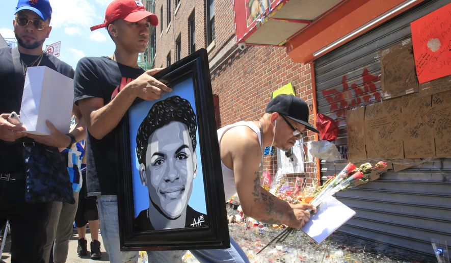 """Jose Bencosme holds a painting of his cousin 15-year-old Lesandro Guzman-Feliz, a gift from celebrity artist Samil Alva, as he visits a community memorial for Feliz who was killed last Wednesday in a machete attack, Tuesday June 26, 2018, in New York. """"I want my painting to bring love, support and unite the community,"""" said Alva, who traveled from his studio in Lawrence, Massachussetts, to present the portrait to Feliz's family. (AP Photo/Bebeto Matthews)"""