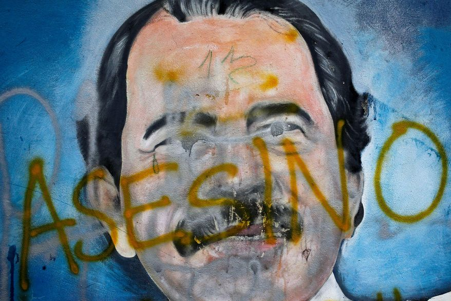 """The Spanish word for """"Murderer"""" covers a mural of Nicaraguan President Daniel Ortega as part of anti-government protests. On July 5, 2018, the Trump administration announced it was levying Magnitsky Act sanctions against three members of the Ortega regime, citing human-rights abuses. (Associated Press/File) **FILE**"""