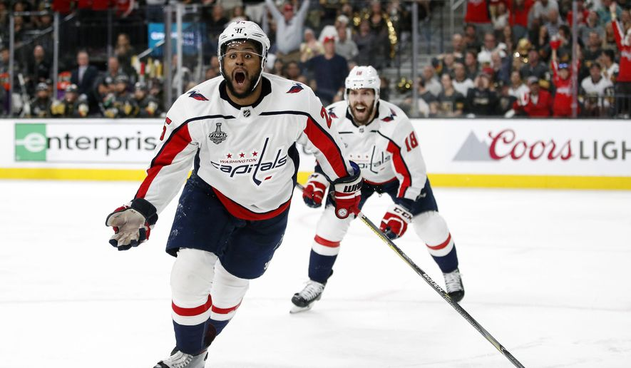FILE - In this June 7, 2018, file photo, Washington Capitals right wing Devante Smith-Pelly, left, celebrates his goal, in front of center Chandler Stephenson during the third period in Game 5 of the NHL hockey Stanley Cup Finals against the Vegas Golden Knights, in Las Vegas. The Capitals have re-signed playoff hero Devante Smith-Pelly to a $1 million, 1-year contract. General manager Brian MacLellan announced the deal Thursday, June 28, 2018, less than 72 hours after not tendering a qualifying offer to the restricted free agent forward. (AP Photo/John Locher, File) **FILE**