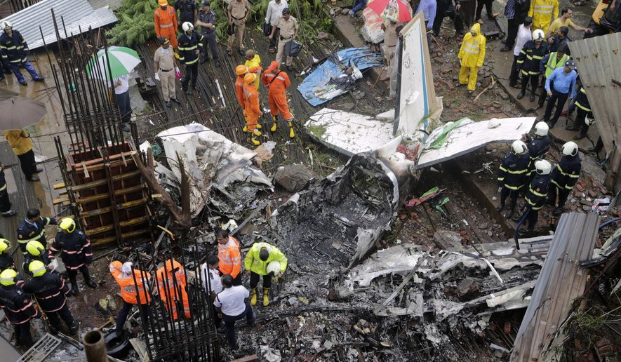 Rescuers stand amid the wreckage of a private chartered plane that crashed in Ghatkopar area, Mumbai, India, Thursday, June 28, 2018. The plane hit an open area at a construction site for a multistory building in a crowded area with many residential apartments. (AP Photo/Rajanish Kakade)