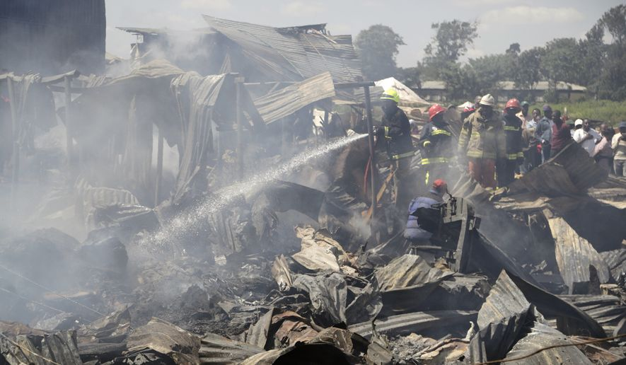 A firefighter damps down the charred debris after a fire swept through a marketplace in Nairobi, Kenya, Thursday June 28, 2018. Authorities report that several people are known to have died and about 70 are receiving hospital treatment, with rescue teams still searching for more bodies and survivors in the market. (AP Photo/Khalil Senosi)