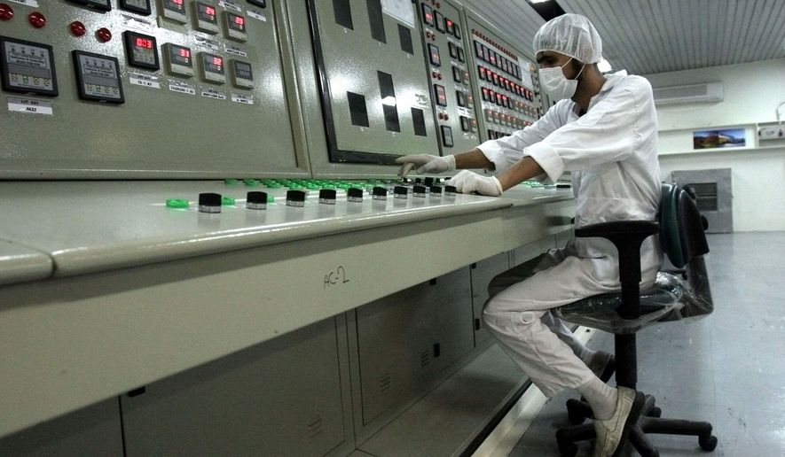 """FILE - In this Feb. 3, 2007 file photo, an Iranian technician works at the Uranium Conversion Facility just outside the city of Isfahan, Iran, 255 miles (410 kilometers) south of the capital Tehran. Iran says it restarted the production facility in Isfahan, a """"major"""" uranium facility involved in its nuclear program, but still pledges to follow the terms of its atomic deal now threatened by President Donald Trump pulling America from the accord. (AP Photo/Vahid Salemi, File)"""