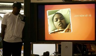 FILE - In this Dec. 23, 2015 file photo, a recent photo of Jahi McMath is shown on a video screen next to her uncle Timothy Whisenton at a news conference in San Francisco. New Jersey officials say McMath, the girl at the center of the medical and religious debate over brain death, has died from excessive bleeding. The girl's mother said Thursday, June 28, 2018, that New Jersey doctors declared Jahi McMath dead after an operation to treat an intestinal issue. A California coroner in 2013 ruled the then 13-year-old died after suffering irreversible brain damage during an operation to remove her tonsils. Her family did not accept the decision and opted to move her to New Jersey. (AP Photo/Jeff Chiu, file)