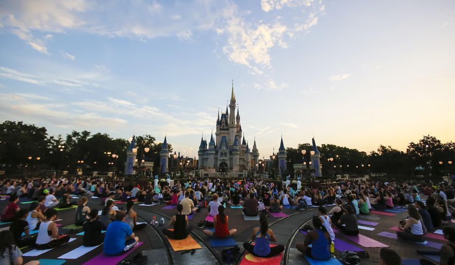 ADVANCE FOR WEEKEND EDITIONS, JUNE 30-JULY 1 - In this Thursday morning, June 21, 2018 photo, more than a thousand Disney cast members do yoga in front of Cinderella's Castle at the Magic Kingdom as the sun rises on International Yoga Day at the theme park in Lake Buena Vista, Fla. (Jacob Langston/Orlando Sentinel via AP)