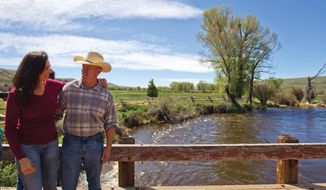 In a May 26, 2018 photo, Gov. Matt Mead and his wife, Carol, talk together on a bridge on their ranch in Albany County, Wyo.  (Shannon Broderick/Laramie Boomerang via AP)