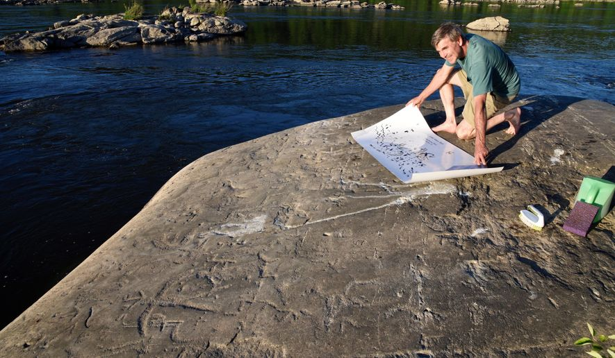 Paul Nevin, an expert on Native American petroglyphs, consults a map of about 150 carvings on Little Indian Rock on Tuesday, June 19, 2018, near the Safe Harbor Dam, Lancaster County, Pa.   There are about 300 carvings on seven mica schist rocks amid a jumble of other rocks out here in the middle of the river. It is believed they were carved by Shenks Ferry Native Americans, using simple stone tools over a period from 500 to 1,000 years ago.  (Ad Crable /LNP via AP)