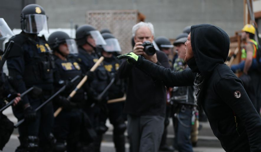 Authorities take action to reopen Portland's Immigration and Customs Enforcement headquarters early Thursday, June 28, 2018 in Portland, Ore. Federal officers arrested eight protesters while trying to reopen the building, that has been closed for more than a week because of a round-the-clock demonstration.  (Mark Graves/The Oregonian via AP) **FILE**