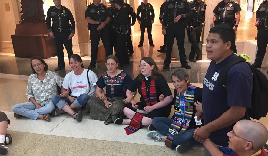 Protesters from faith-based groups gathered inside the state Capitol to condemn Republican New Mexico Gov. Susana Martinez's support for federal immigration policies Thursday, June 28, 2018, in Santa Fe, N.M. The protestors ignored requests to leave as the building was closed to visitors. At least three were arrested by state police who provide security for the governor. (AP Photo/Morgan Lee)
