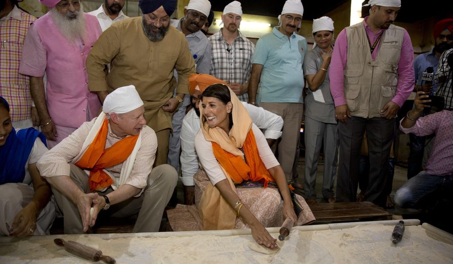U.S. Ambassador to the United Nations Nikki Haley, center, talks with U.S. ambassador to India Kenneth I. Juster while they try their hands on making Indian bread during their visit to a Gurdwara Sis Ganj Sahib, a Sikh temple, in New Delhi, India, Thursday, June 28, 2018. Nikki Haley offered inter-faith prayers in New Delhi on Thursday, visiting a Sikh shrine, a Hindu temple, a Jain temple, a Church and a Muslim mosque in the old, walled area of the Indian capital. The United States on Wednesday announced postponement of a high-level dialogue with India scheduled for next week in Washington, D.C., without assigning any reasons even as its ambassador to the United Nations met with top Indian leaders in New Delhi to step up ties in various fields. (AP Photo/Manish Swarup)