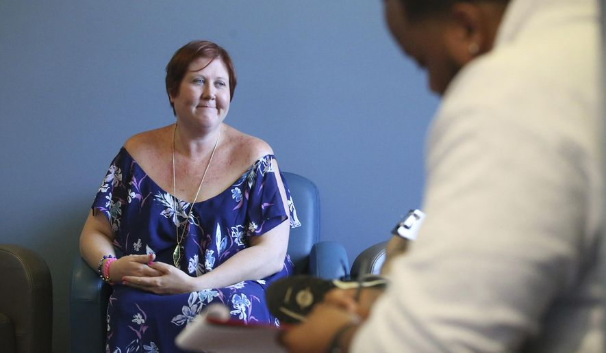 In this Wednesday, June 27, 2018 photo, Whitney Wehmeyer, CEO of the Tulsa Higher Care Clinic, talks with potential patients as they fill out paperwork in Tulsa, Okla. The clinic opened in Tulsa just hours after Oklahoma voters approving medical marijuana, although it will likely be weeks before residents can apply for a license to possess marijuana for medical purposes. Voters approved medical marijuana Tuesday. (Matt Barnard/Tulsa World via AP)