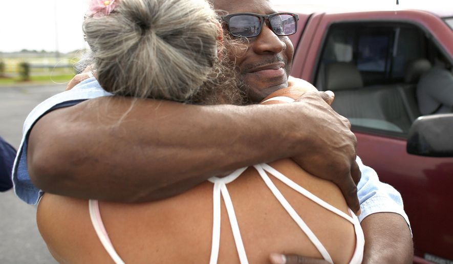 "In this Wednesday, June 27, 2018 photo, Lenny Singleton and his wife Vandy embrace after Singleton was released from St. Bride's prison in Chesapeake. Va., following his January, 2018 pardoned by then-Gov. Terry McAuliffe. In the 1990s, a Norfolk judge sentenced Singleton to two life terms plus 110 years in prison for a series of ""grab and dash"" robberies in which no one was injured and Singleton made off with only $550. Singleton says he blames himself for the crimes, but McAuliffe said in his pardon that the court had ""unjustly imposed a deeply severe punishment."" (Stephen M. Katz/The Virginian-Pilot via AP)"