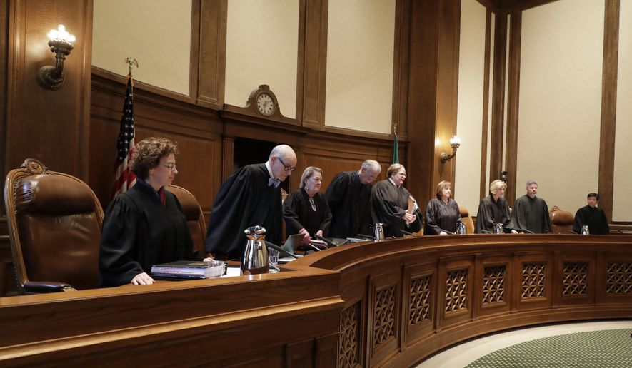 The justices of the Washington Supreme Court take their seats, Thursday, June 28, 2018, at the start of a session where they were scheduled to hear arguments in Olympia, Wash., over whether state lawmakers acted constitutionally when they passed a new state law designed to improve police training in de-escalation tactics and make it easier to prosecute officers for negligent shootings. (AP Photo/Ted S. Warren)