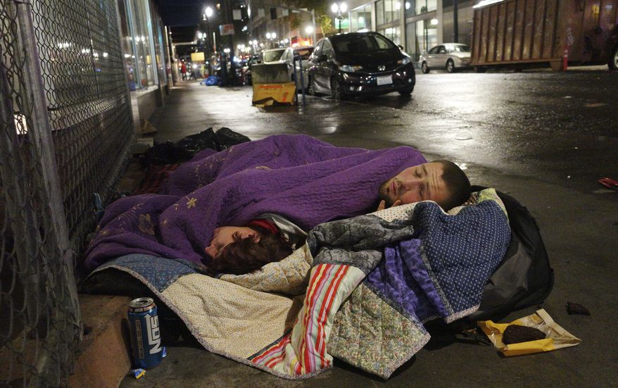 FILE--In this Sept. 18, 2017, file photo, Taz Harrington, right, sleeps with his girlfriend, Melissa Ann Whitehead, on a street in downtown Portland, Ore. A recent analysis found that one in every two arrests made by the Portland Police Bureau last year was of a homeless person. (AP Photo/Ted S. Warren, file)