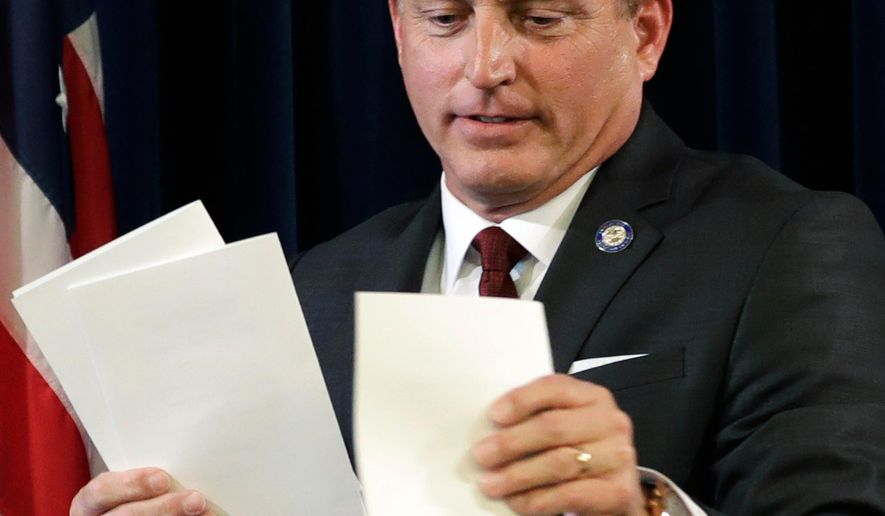 """FILE - In this Dec. 19, 2016, file photo, Iowa Secretary of State Paul Pate collects ballots during Iowa's Electoral College vote at the Statehouse in Des Moines, Iowa. Nearly 1 percent of voters in Iowa's largest counties did not show identifications during the June 5 primary, an early sign that the new voter ID law could have some impact when it takes full effect next year. As part of a gradual rollout of the ID requirements, voters without them in 2018 are being allowed to sign an """"Oath of Identification"""" attesting that they are who they say they are. Pate has argued that the identification requirements will improve the integrity of elections. (AP Photo/Charlie Neibergall, File)"""