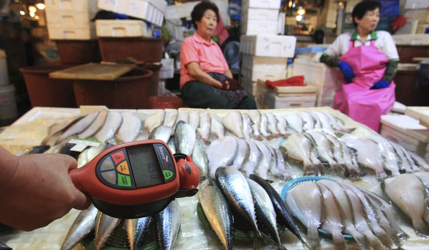 FILE - In this Sept. 6, 2013, file photo, a worker using a Geiger counter checks for possible radioactive contamination at Noryangjin Fisheries Wholesale Market in Seoul, South Korea. South Korea said Friday, Feb. 23, 2018, it will appeal the World Trade Organization's decision against Seoul's import bans on Japanese fishery products imposed in the wake of Fukushima nuclear meltdowns. (AP Photo/Ahn Young-joon. File)