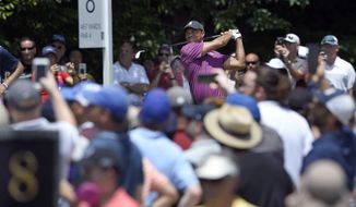 Tiger Woods, top center, watches his tee shot on the eighth hole during the second round of the Quicken Loans National golf tournament, Friday, June 29, 2018, in Potomac, Md. (AP Photo/Nick Wass) ** FILE **