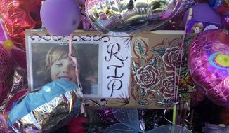 FILE - In this Aug. 29, 2016, file photo, a photo of Victoria Martens, a 10-year-old Albuquerque girl who was brutally murdered, is placed in a memorial outside her apartment in Albuquerque, N.M. New Mexico prosecutors have dismissed murder and sexual assault charges against the man arrested two years ago in the death of the 10-year-old Albuquerque girl whose dismembered remains were found in her family's apartment, Friday, June 29, 2018. (AP Photo/Russell Contreras, File)
