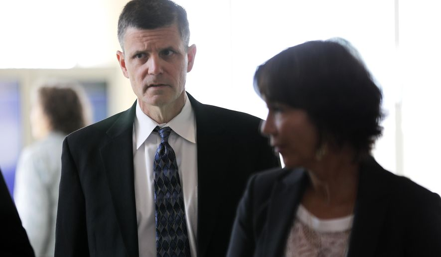 Former Washington state Auditor Troy Kelley, left, walks through a lobby at the federal courthouse in Tacoma, Wash., Friday, June 29, 2018, before a sentencing hearing following his conviction in 2017 on several charges related to when he ran a real-estate escrow services business during the height of last decade's housing boom. (AP Photo/Ted S. Warren)