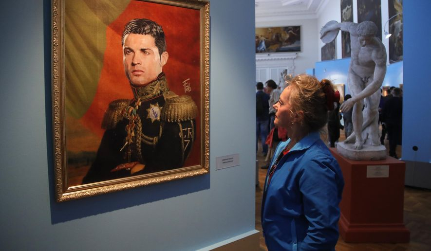 """FILE - In this Wednesday, June 20, 2018 file photo, a woman watches a portrait of Portugal's soccer star Cristiano Ronaldo, part of the """"Like The Gods"""" exhibition at the Museum of the Russian Academy of Arts in St. Petersburg, Russia. It's a collection of digitally made portraits of around 40 modern soccer superstars dressed in military and royal uniforms dating back to the 19th century. (AP Photo/Dmitri Lovetsky, File)"""