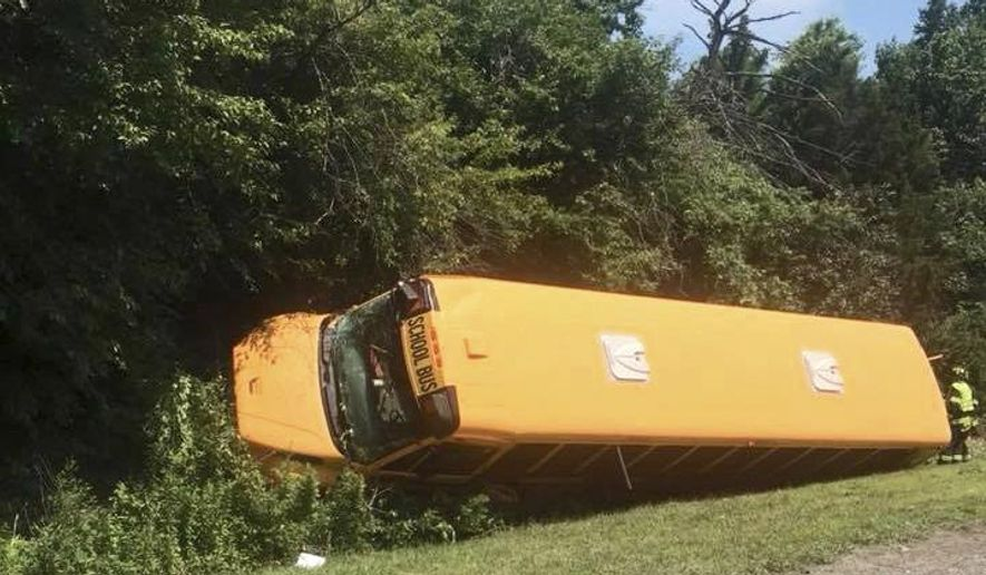 This image provided by Dena Lynn shows a school bus that crashed and overturned Friday, June 29, 2018, on the New Jersey Turnpike in Cherry Hill, N.J. Roughly 30 people were aboard the bus, including several children who had minor injuries and were treated at a hospital, but no serious injuries were reported. (Dena Lynn via AP)