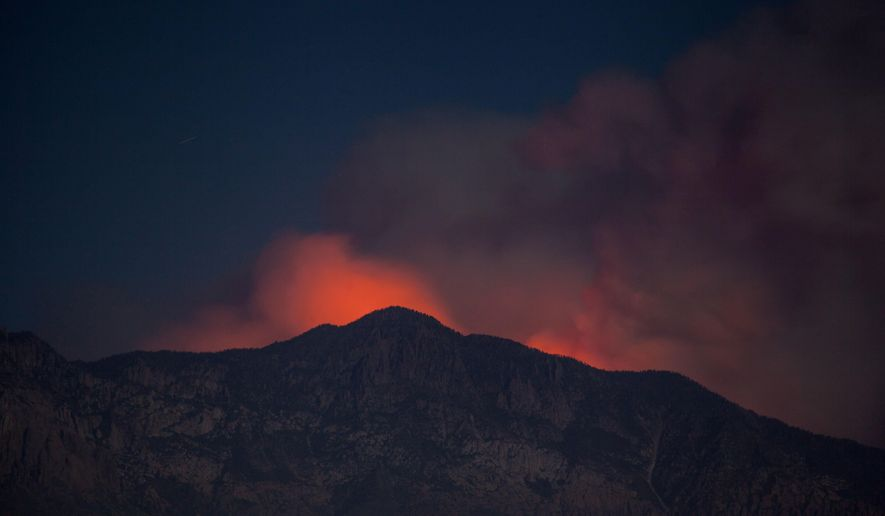Smoke and glow from a wildfire is seen from Washington City, Utah, Thursday, June 28, 2018. Firefighters were battling more than a half dozen wild land blazes across Utah in record heat and windy conditions on Thursday.(Chris Caldwell/The Spectrum via AP)
