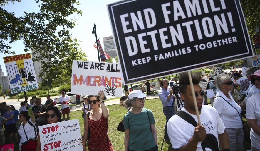 People gather to protest against President Donald Trump's immigration policies at Logan Square in Philadelphia, Saturday, June 30, 2018. Hundreds of thousands of protesters have packed rallies across the United States to demand an end to family separations at the U.S.-Mexico border.  (Tim Tai/The Philadelphia Inquirer via AP)
