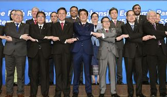 Japanese Prime Minister Shinzo Abe, center, joins hands with trade ministers from Asian countries for a group photo during the Regional Comprehensive Economic Partnership (RCEP) meeting in Tokyo Sunday, July 1, 2018. Trade ministers from 16 Asian countries are meeting in Tokyo on a regional trade pact, highlighting efforts to ensure free and rules-based commerce in the face of an increasingly protectionist United States under President Donald Trump. (Sadayuki Goto/Kyodo News via AP)