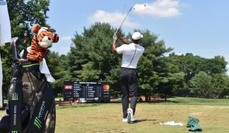 Tiger Woods hits range balls before the third round of the Quicken Loans National at TPC Potomac at Avenel Farm in Potomac, Md. on Saturday, June 30, 2018. The bag in the foreground will be autographed and auctioned off to benefit the charitable works of the TGR Foundation. (Photo courtesy of Quicken Loans National)